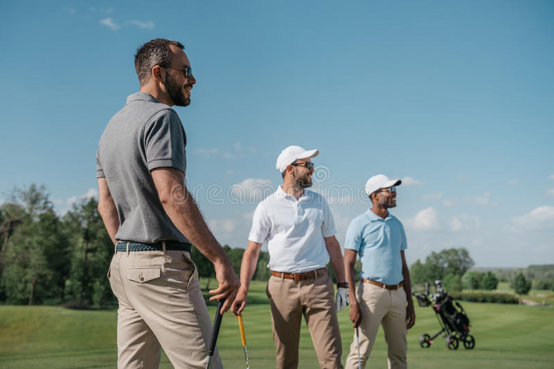 Multiethnic golf players looking away while standing on pitch stock photos