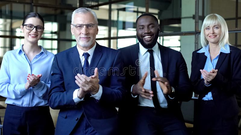 Multiethnic group of business people applauding looking camera, congratulations. Stock photo royalty free stock photo