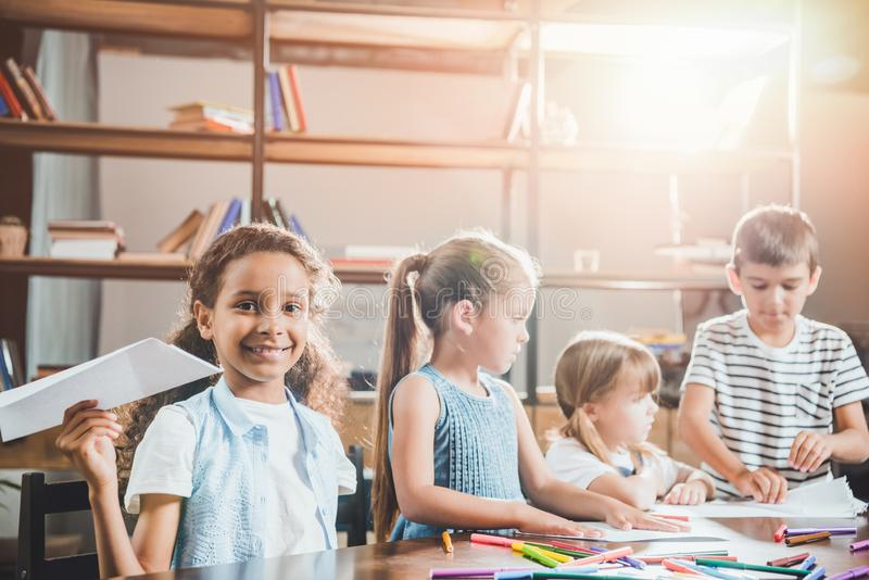 Multiethnic group of children drawing pictures together. At home royalty free stock photography