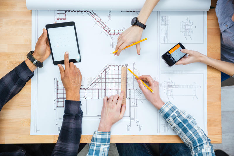 Multiethnic group of designers working with blueprint stock image multiethnic group of designers making calculations and working with blueprint using tablet and smartphone malvernweather Image collections