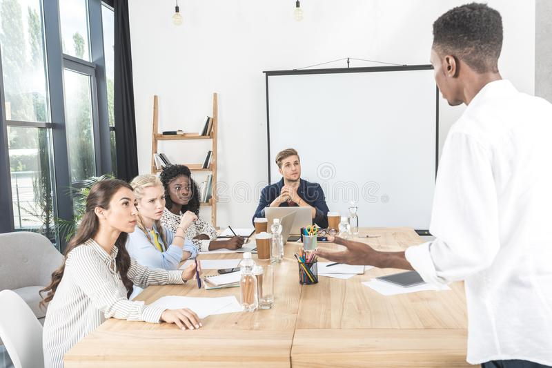 multiethnic group of focused colleagues listening to african royalty free stock image