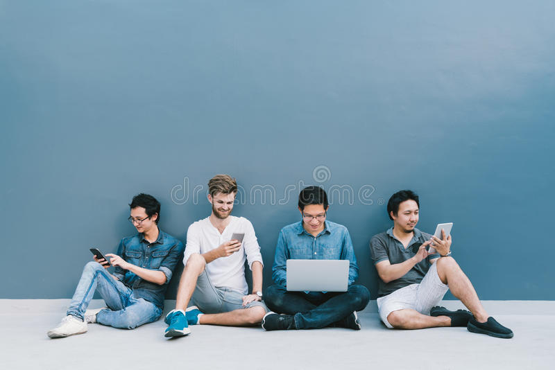 Multiethnic group of four men using smartphone, laptop computer, digital tablet together with copy space on blue wall stock photos