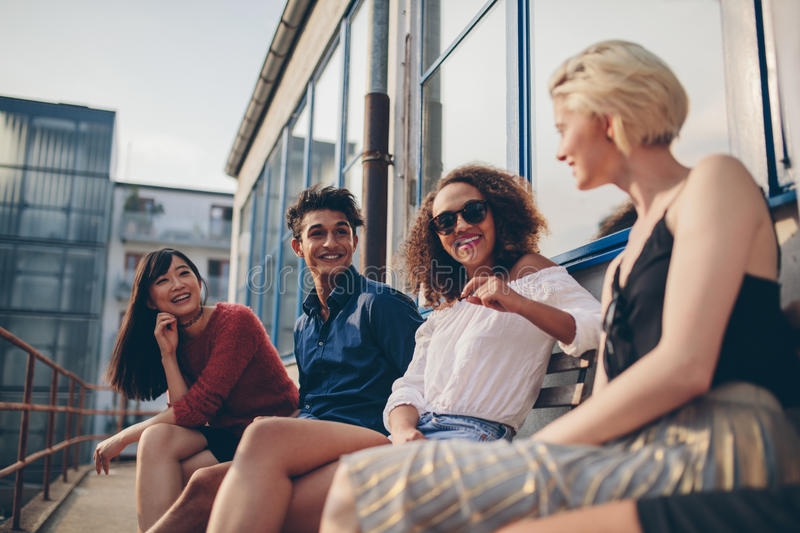 Multiethnic group of friends in balcony and talking. Shot of multiethnic group of friends sitting in balcony and talking. Young people relaxing outdoors in stock photography