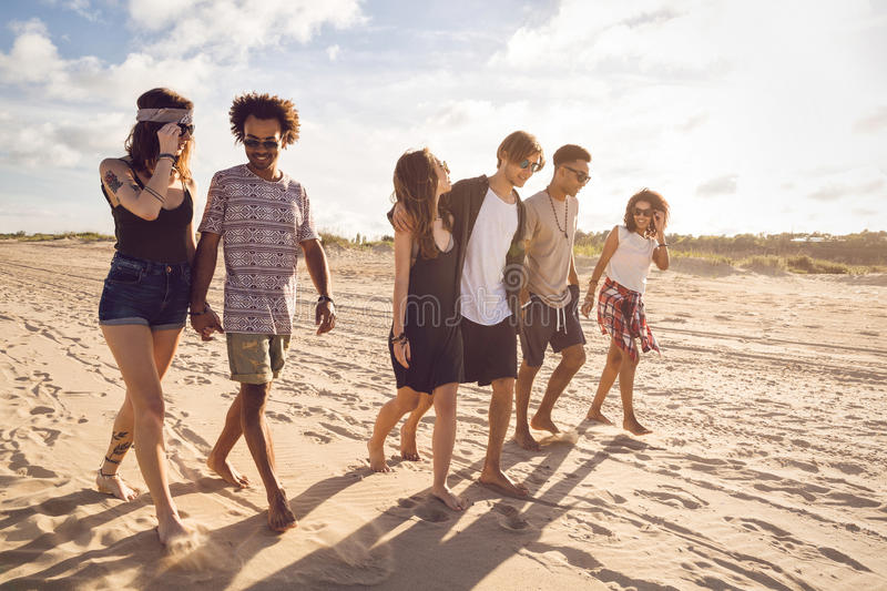 Multiethnic group of friends walking on the beach royalty free stock image