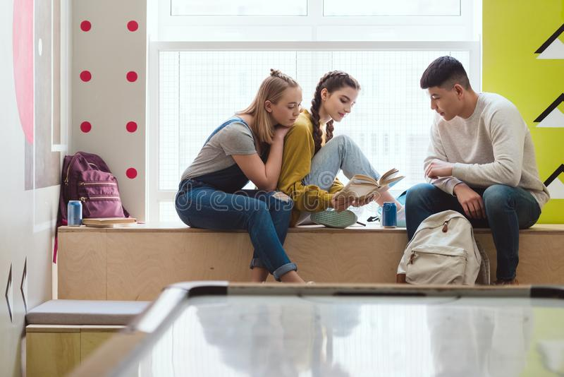 Multiethnic group of high school students reading book during. School break stock images