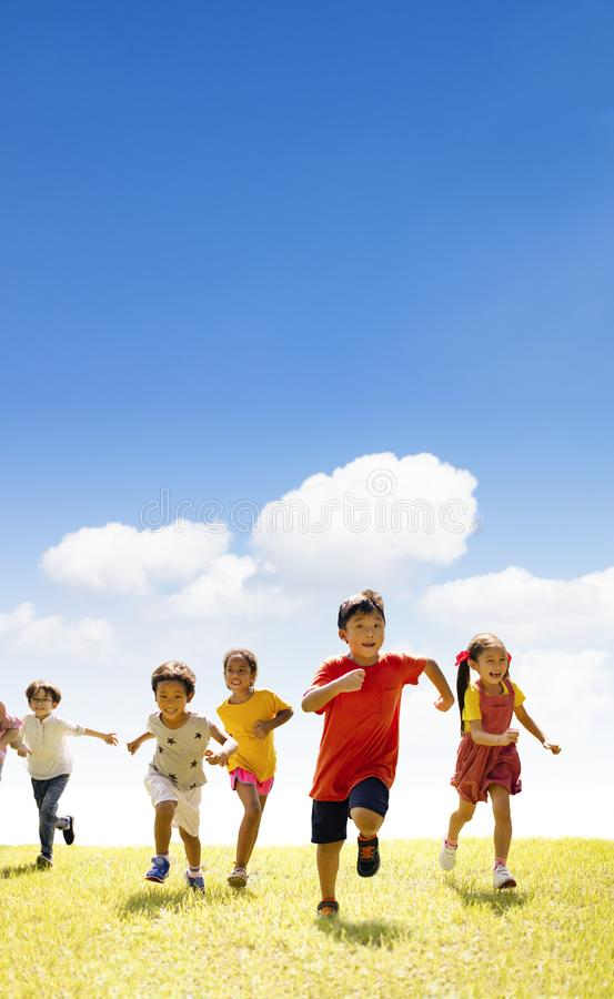 Multiethnic group of school children running on the grass royalty free stock photography