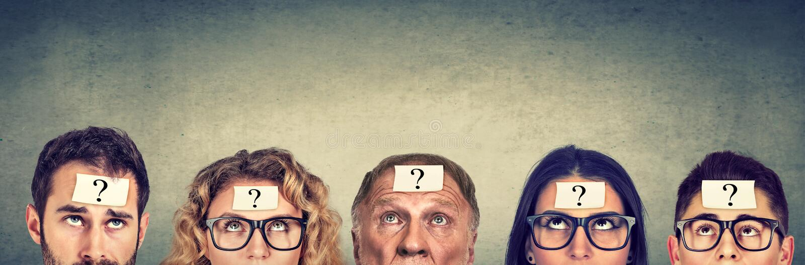 Multiethnic group of thinking people with question mark looking up. Multiethnic group of thinking people men and women with question mark looking up royalty free stock image