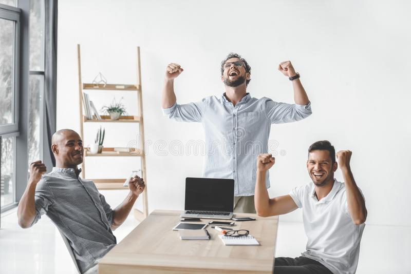 multiethnic group of young business people celebrating success at workplace stock images