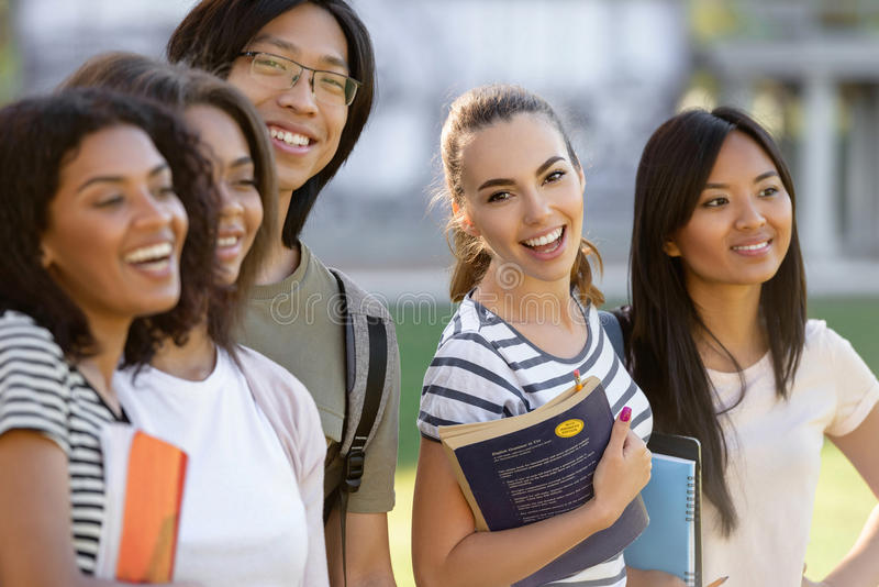 Multiethnic group of young happy students standing outdoors. stock photos