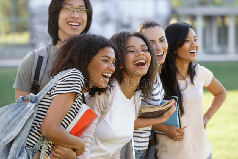 Multiethnic group of young happy students standing outdoors. royalty free stock image