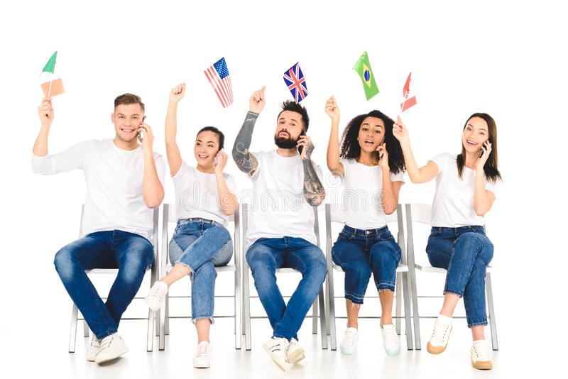 Multiethnic group of young people talking on smartphones and holding flags above heads isolated. On white royalty free stock image