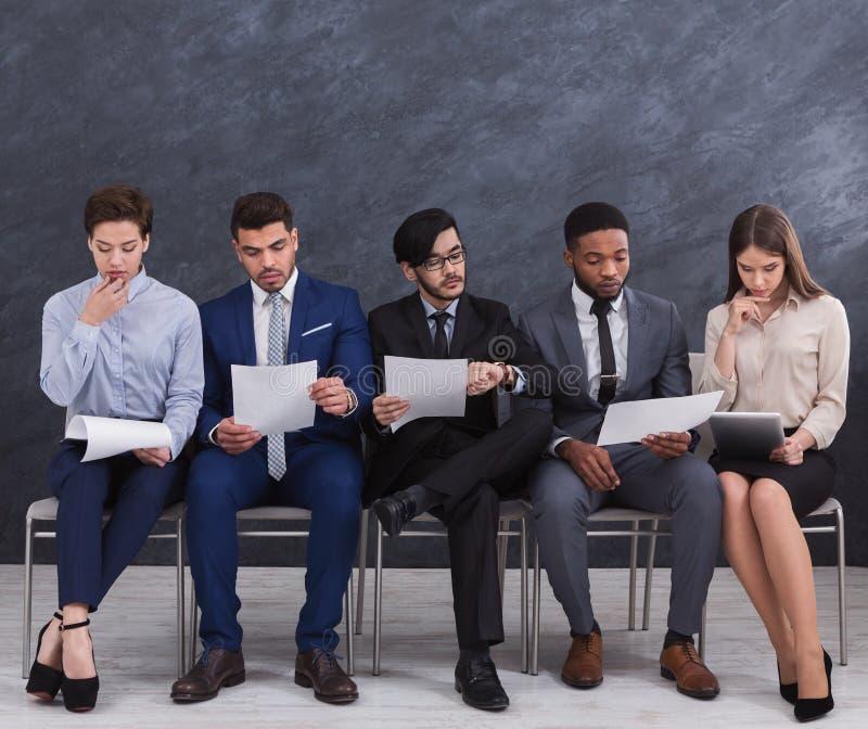 Multiethnic job candidates preparing for job interview stock photo