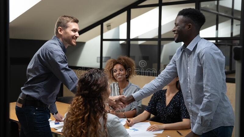 Multiethnic male colleagues handshake greeting at briefing stock photography