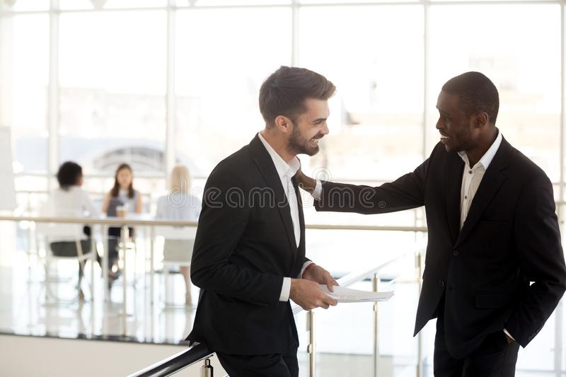 Multiethnic male employees standing in hallway laughing at joke stock images