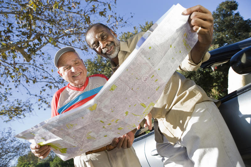 Multiethnic Male Friends With Roadmap. Multiethnic male mature friends with roadmap standing by car stock photos