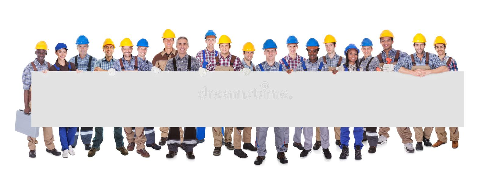 Multiethnic manual workers holding blank banner royalty free stock photo