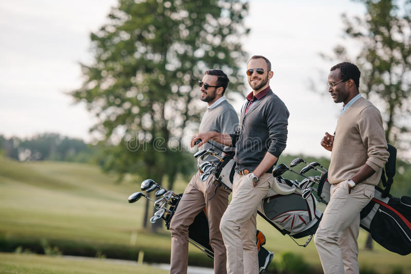 Multiethnic men holding bags with golf clubs and walking on golf course royalty free stock photos