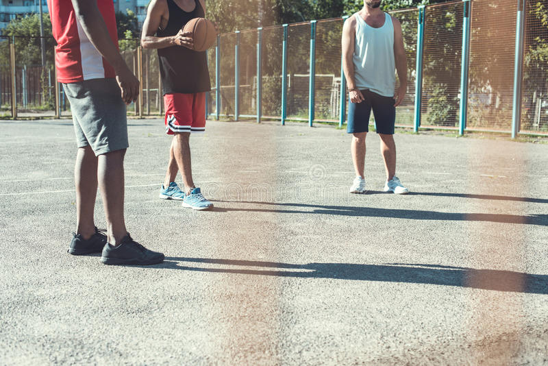 Multiethnic men playing basketball on court. Partial view of multiethnic men playing basketball on court stock image
