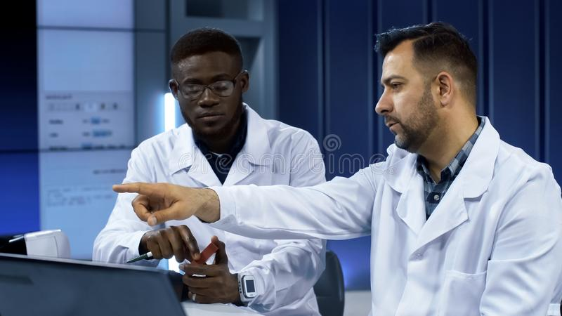 Scientists investigating 3-D printed model. Multiethnic men in white gown discussing usage of three-dimensional printing in manufacturing process while exploring stock photography