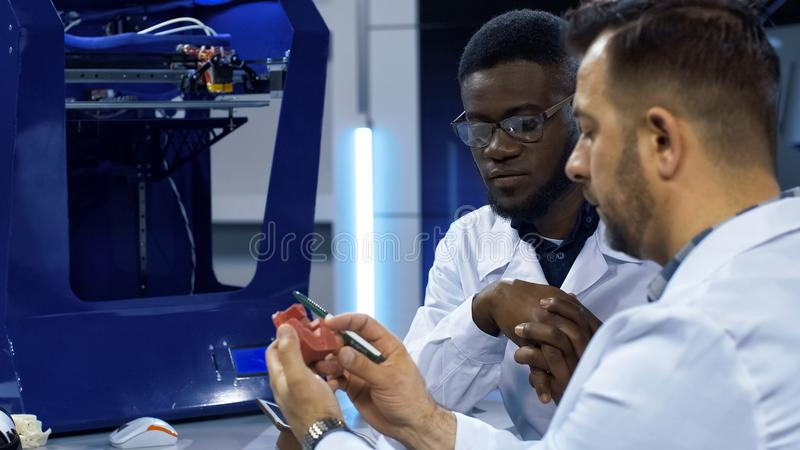 Scientists investigating 3-D printed model. Multiethnic men in white gown discussing usage of three-dimensional printing in manufacturing process while exploring royalty free stock photography