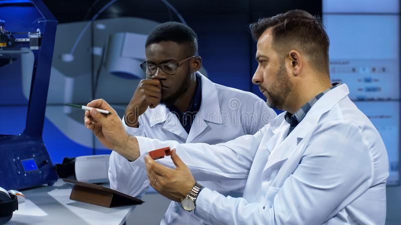 Scientists investigating 3-D printed model. Multiethnic men in white gown discussing usage of three-dimensional printing in manufacturing process while exploring stock photo