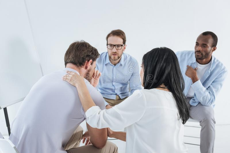 Multiethnic mid adult people sitting on chairs and supporting upset man. Multiethnic mid adult people sitting on chairs and supporting upset men during anonymous vector illustration
