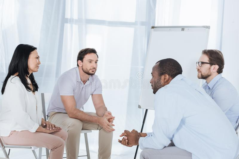multiethnic middle aged people sitting on chairs during anonymous group royalty free stock image
