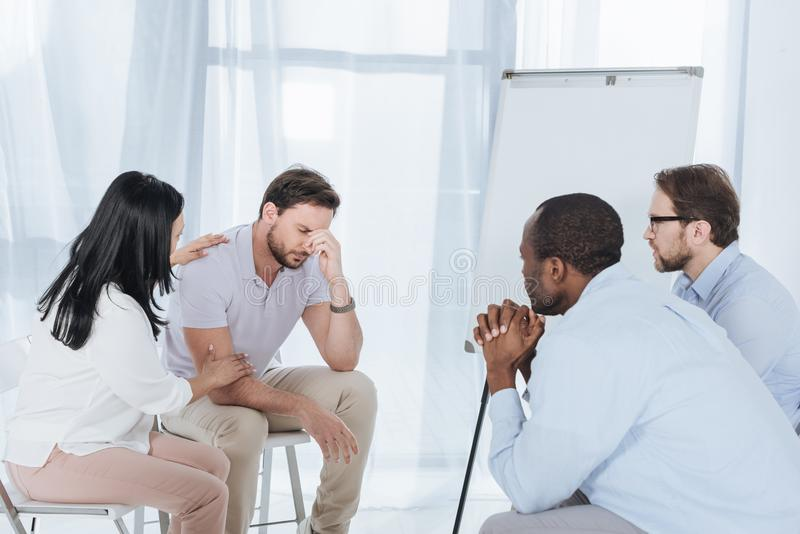 multiethnic middle aged people sitting on chairs and supporting upset man stock images