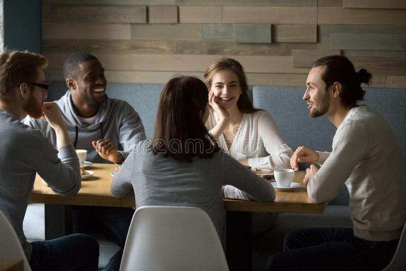 Diverse happy friends having fun sitting in cafe royalty free stock photo