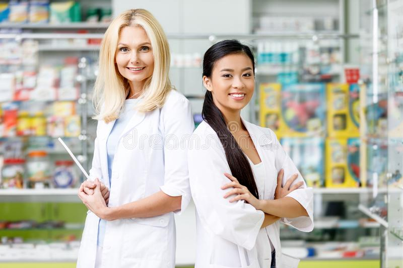 Multiethnic pharmacists in white coats standing with crossed arms and smiling at camera. In drugstore stock photo