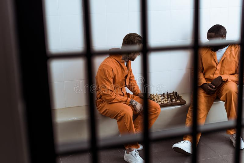 multiethnic prisoners playing chess behind stock photos