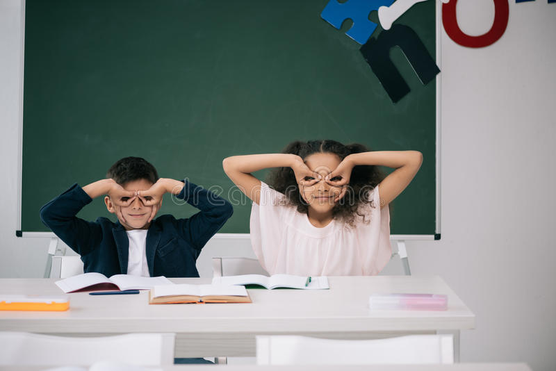 Multiethnic pupils having fun while sitting together at desk in class stock image