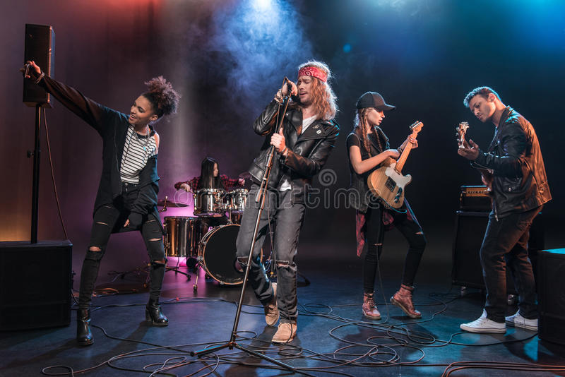 Multiethnic rock and roll band performing music on stage. Young multiethnic rock and roll band performing music on stage royalty free stock image