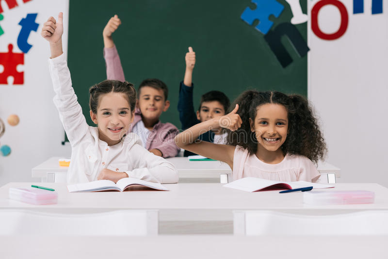 Multiethnic schoolkids showing thumbs up while sitting at desks in classroom. Cheerful multiethnic schoolkids showing thumbs up while sitting at desks in stock image