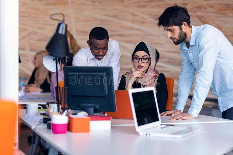 Multiethnic startup business team on meeting in modern bright office interior brainstorming, working on laptop and royalty free stock photos
