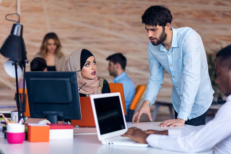 Multiethnic startup business team on meeting in modern bright office interior brainstorming, working on laptop and stock image