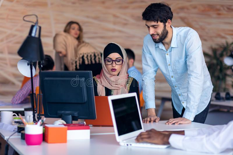 Multiethnic startup business team on meeting in modern bright office interior brainstorming, working on laptop and stock images