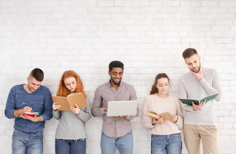 Multiethnic students studying, preparing for exam against white wall stock images