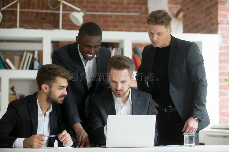 Multiethnic team of corporate employees looking at laptop screen. Businessman pointing at computer screen, african american colleague smiling. Group of royalty free stock photo