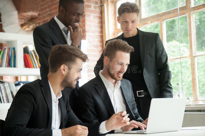 Multiethnic team of corporate employees looking at laptop screen. Businessman typing on computer screen, african american colleague smiling. Group of coworkers royalty free stock images