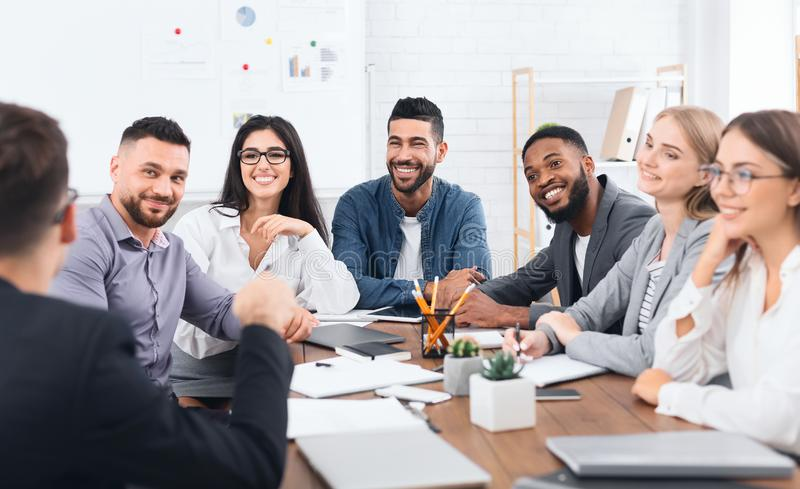 Multiethnic team listening to leader speaking at meeting stock image