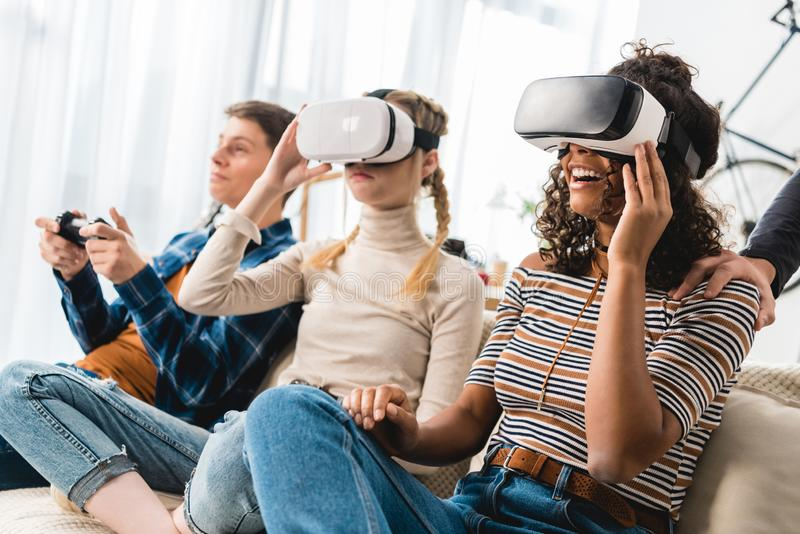 Multiethnic teen girls watching something with virtual reality. Headsets royalty free stock image