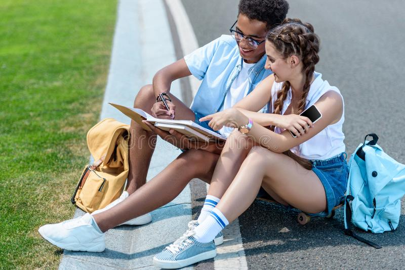 multiethnic teenage boy and girl studying together stock images