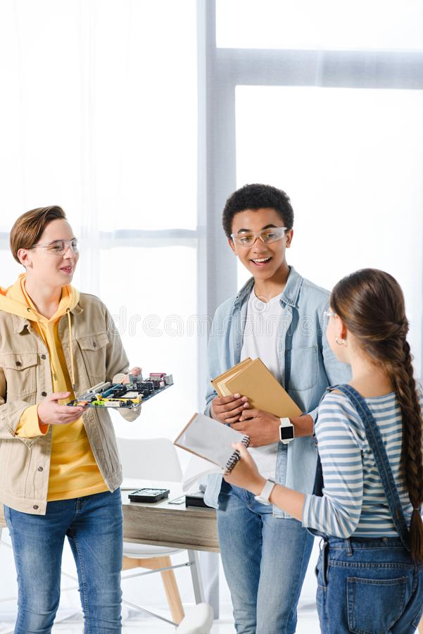 Multiethnic teenagers holding computer motherboard and books. At home royalty free stock images