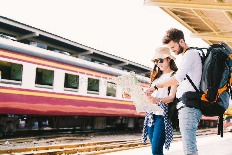 Multiethnic traveler couple using generic local map navigation together at train station platform. Asia tourism trip concept. Multiethnic traveler couple royalty free stock photo
