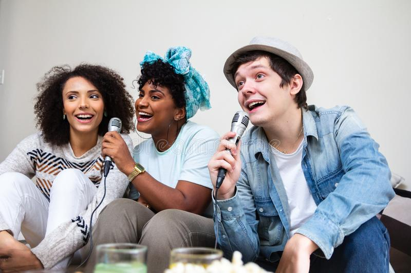 University rommates singing together karaoke in living room. Cheerful, happy youth moment. Multiethnic university rommates singing together karaoke in living stock photography