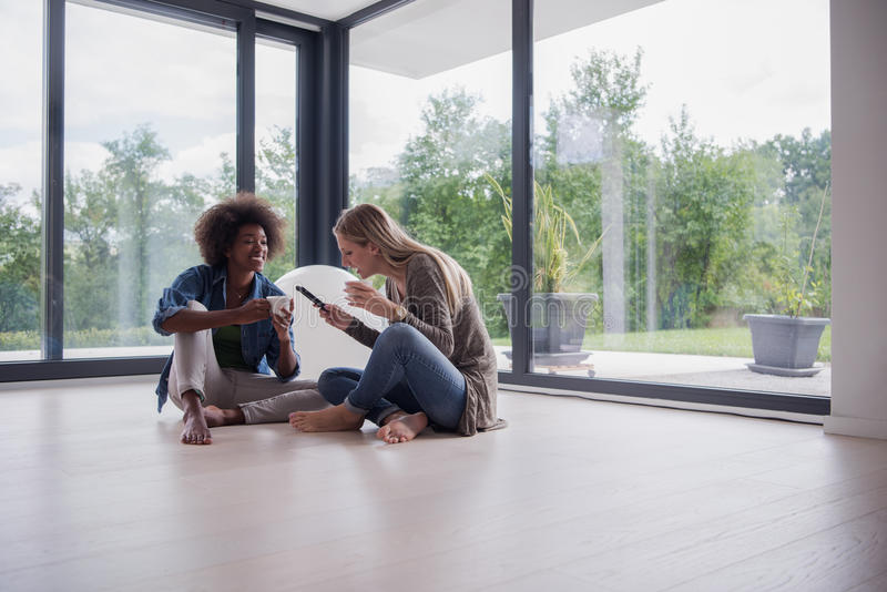 Download Multiethnic Women Sit On The Floor And Drinking Coffee Stock Photo - Image: 83703694