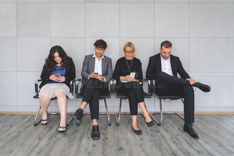 Multiethnic work applicants busy using laptops and smartphones preparing for recruiting talk, diverse job candidates sit in queue stock photos