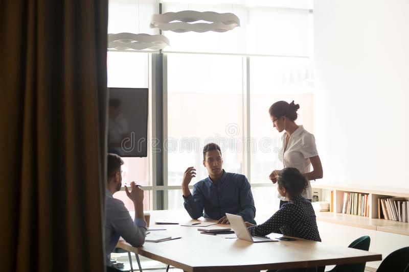 Multiethnic employees discuss ideas with female team leader at meeting royalty free stock images