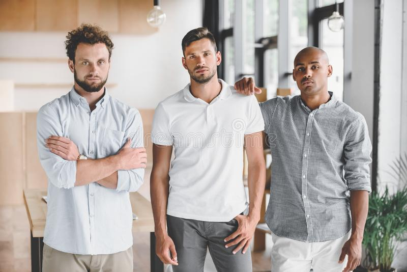 multiethnic young businessmen looking at camera while standing royalty free stock images